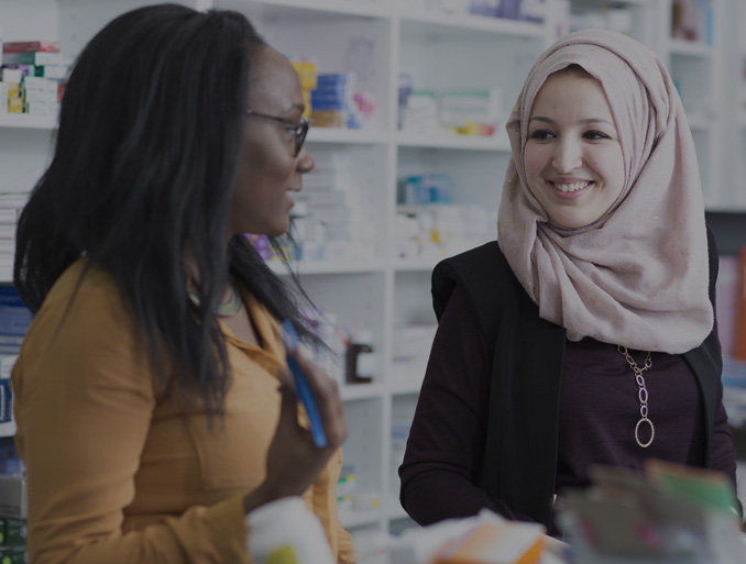 Two female pharmacists talking to each other in a pharmacy.