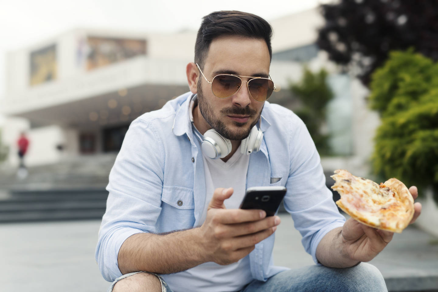 Man eating pizza on the phone